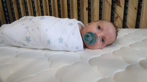 Baby swaddled with transitioning baby to crib