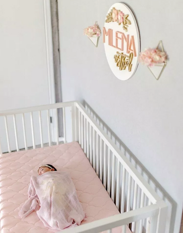 baby girl asleep in a crib on a newton baby crib mattress with a pink mattress cover