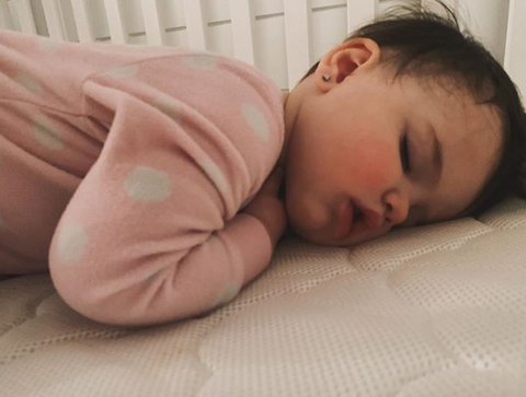 up-close of baby sleeping on stomach
