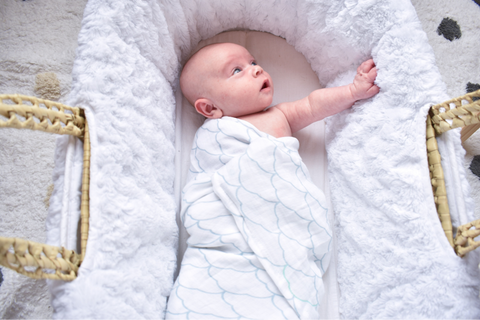 Baby with one arm out of swaddle letting parents know when to stop swaddling