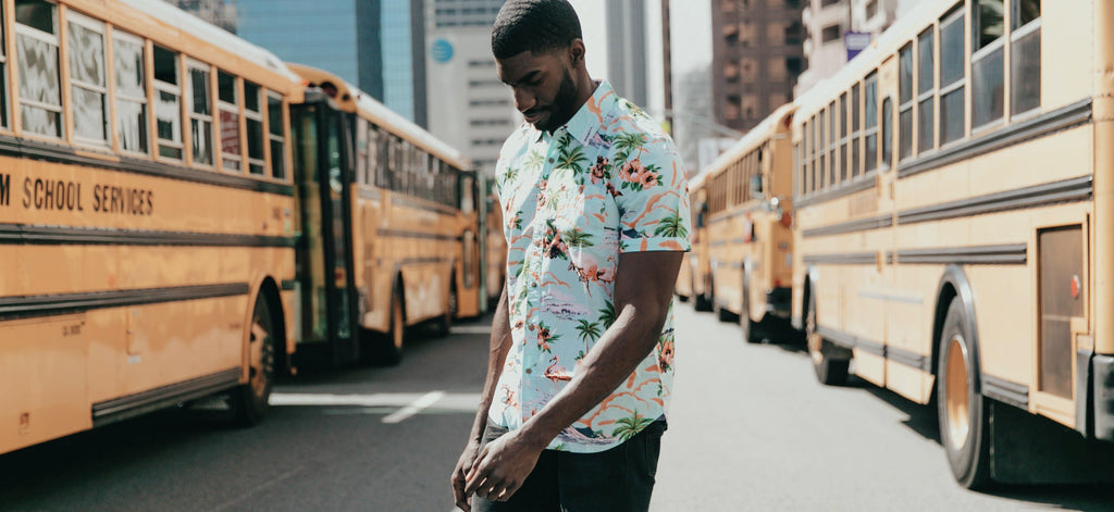 contact form header image, man in tropical shirt standing in front of school buses on city street