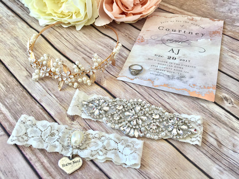 crystal and pearl wedding garter, gold hair vine, with a wedding ring and wedding invitation
