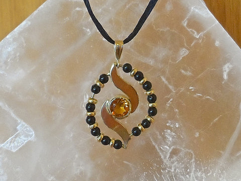 Proton pendant is 1.00 carat rare bright orange fire Citrine, surrounded by black Onyx beads and 14k. gold roundels.