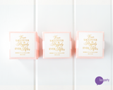 Three pink favor boxes with square gold and white personalized wedding stickers affixed. Lux Party logo.