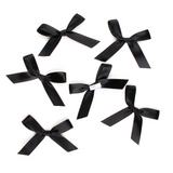 Multiple black satin pre-tied bows by Lux Party, showing peel and stick backing.