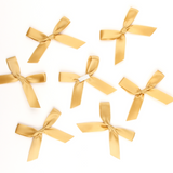 Multiple gold satin pre-tied bows by Lux Party, showing peel and stick backing.