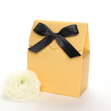 Lux Party's gold favor box with a scalloped edge and a black satin bow next to white ranunculus flowers.