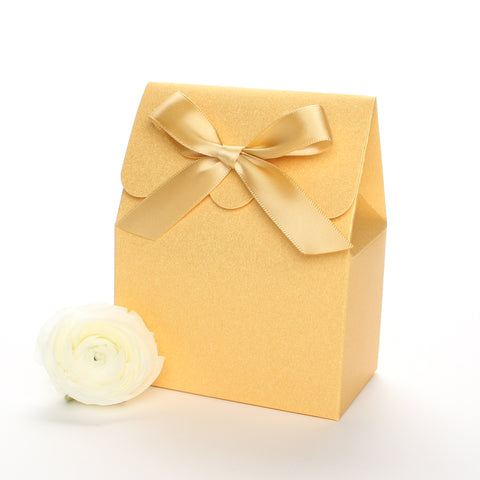 Lux Party's gold favor box with a scalloped edge and a gold satin bow next to white ranunculus flowers.