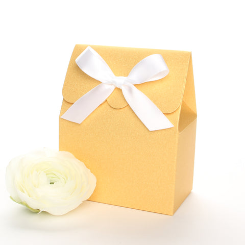 Lux Party's gold favor box with a scalloped edge and a white satin bow next to white ranunculus flowers.