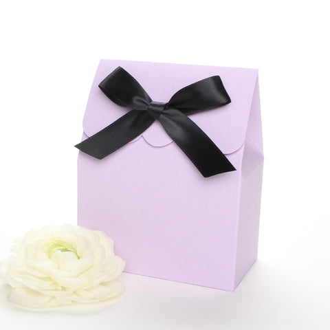 Lux Party's lavender favor box with a scalloped edge and a black satin bow next to pink and white ranunculus flowers.