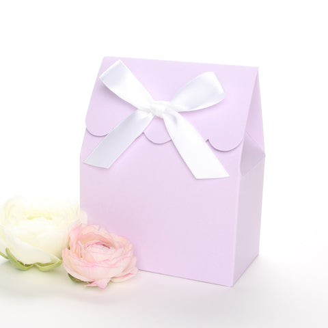 Lux Party's lavender favor box with a scalloped edge and a white satin bow next to pink and white ranunculus flowers.