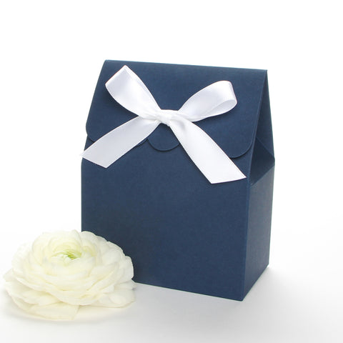 Lux Party's navy blue favor box with a scalloped edge and a white satin bow next to white ranunculus flowers.