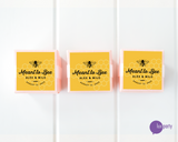 Three pink favor boxes with square yellow meant to bee personalized stickers affixed. Lux Party logo.