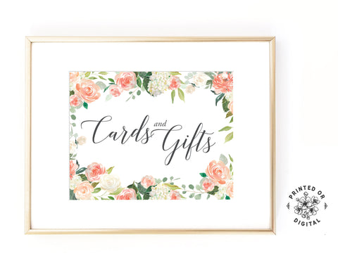 Lux Party's cards and gifts sign, with dark grey script surrounded by pastel flowers, in a gold frame.
