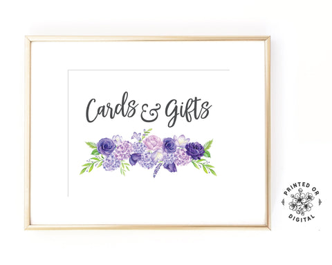 Lux Party's cards and gifts sign, with dark grey script and purple flowers, in a gold frame.