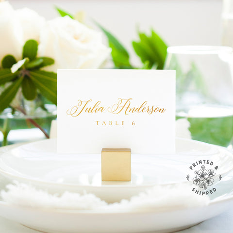 Lux Party's gold place cards with white background and gold lettering, in a wedding table place setting.