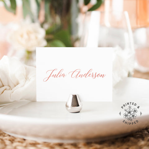Lux Party's rose gold place cards with white background and pink lettering, in a wedding table place setting.