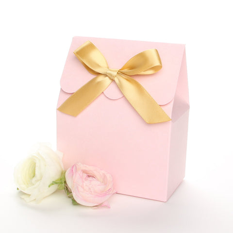 Lux Party's pink favor box with a scalloped edge and a gold bow next to pink and white ranunculus flowers.