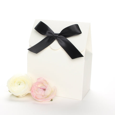 Lux Party's ivory favor box with a scalloped edge and a black satin bow next to pink and white ranunculus flowers.