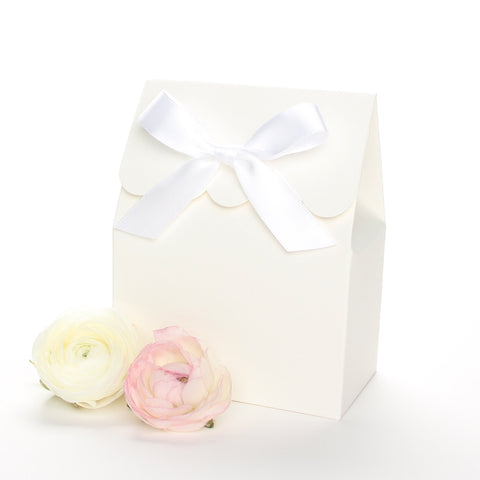 Lux Party's ivory favor box with a scalloped edge and a white satin bow next to pink and white ranunculus flowers.