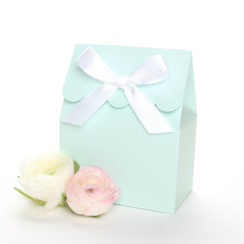 Lux Party's light blue favor box with a scalloped edge and a white satin bow next to pink and white ranunculus flowers.