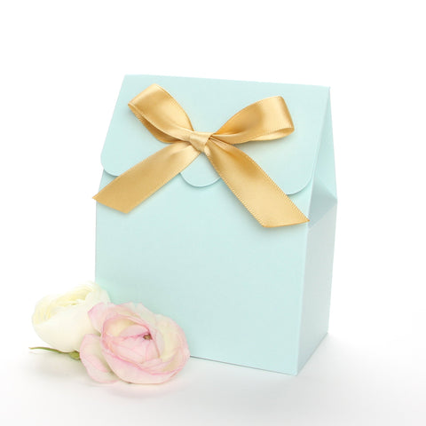 Lux Party's light blue favor box with a scalloped edge and a gold satin bow next to pink and white ranunculus flowers.