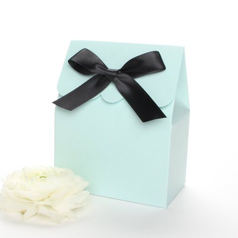 Lux Party's light blue favor box with a scalloped edge and a black satin bow next to white ranunculus flowers.