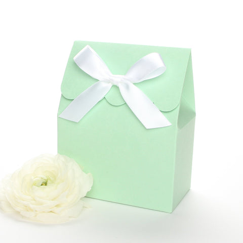 Lux Party's mint green favor box with a scalloped edge and a white satin bow next to white ranunculus flowers.