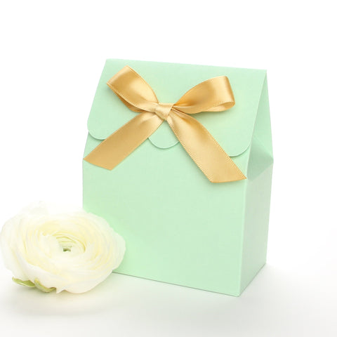 Lux Party's mint green favor box with a scalloped edge and a gold satin bow next to white ranunculus flowers.