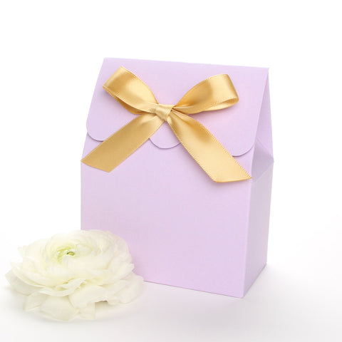 Lux Party's lavender favor box with a scalloped edge and a gold satin bow next to white ranunculus flowers.