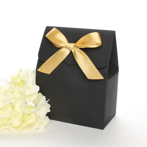 Lux Party's black favor box with a scalloped edge and a gold satin bow next to white hydrangea flowers.