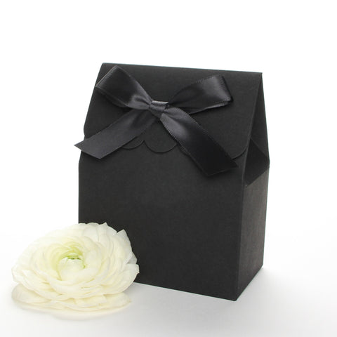 Lux Party's black favor box with a scalloped edge and a black bow next to white ranunculus flowers.
