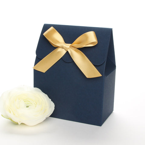 Lux Party's navy blue favor box with a scalloped edge and a gold bow next to white ranunculus flowers.