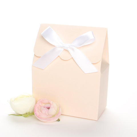 Lux Party's blush favor box with a scalloped edge and a white bow next to pink and white ranunculus flowers.