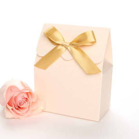 Lux Party's blush favor box with a scalloped edge and a gold bow next to a pink rose.
