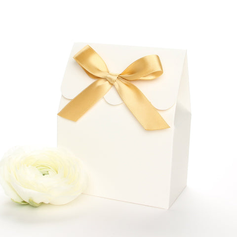Lux Party's ivory favor box with a scalloped edge and a gold satin bow next to white ranunculus flowers.