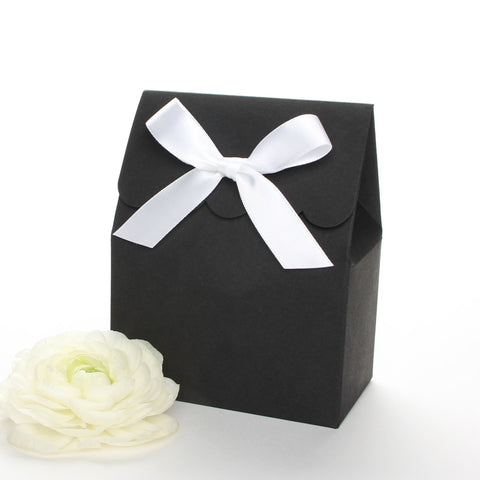 Lux Party's black favor box with a scalloped edge and a white satin bow next to white ranunculus flowers.