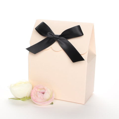 Lux Party's blush favor box with a scalloped edge and a black bow next to white ranunculus flowers.