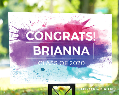 Lux Party's congrats graduation lawn sign with bright paint splotches background, in an outdoor setting.