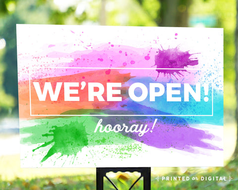 Lux Party's we're open lawn sign with bright paint splatter background, in an outdoor setting.
