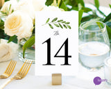 Lux Party's white table number card with black numbers and a greenery sprig, at a wedding table place setting. Lux party logo.