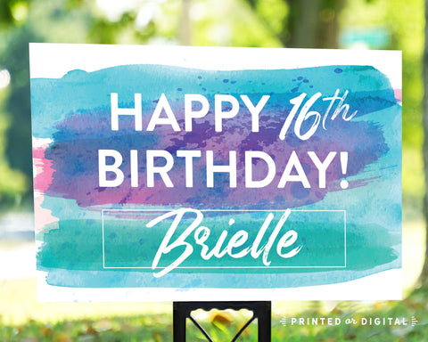 Lux Party's happy birthday lawn sign with bright blue and purple brushstrokes background, in an outdoor setting.