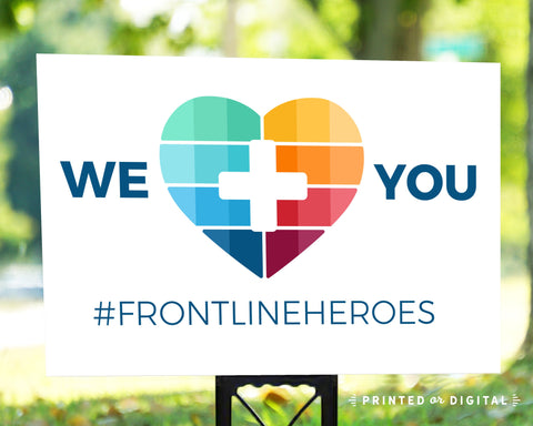 Lux Party's we heart you frontline heroes lawn sign with colorful heart, in an outdoor setting.