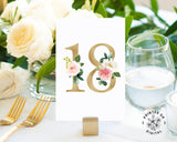 Lux Party's white table number card with gold numbers and pastel flowers, at a wedding table place setting.