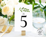 Lux Party's white table number card with black numbers and a greenery sprig, at a wedding table place setting.