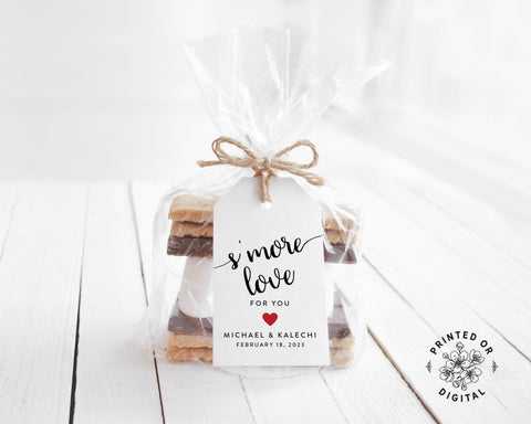 Lux Party's white s'more love wedding favor tag with black script and a red heart, tied to a clear favor bag of s'mores ingredients.