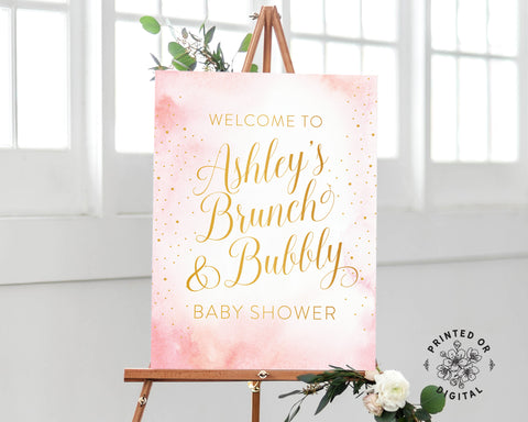 Lux Party's brunch and bubbly baby shower welcome sign, with a pink watercolor background and gold lettering, on a wooden easel.