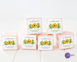 Six pink favor boxes with let love grow sunflower wedding stickers affixed. Lux Party logo.