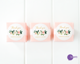 Three pink favor boxes with round floral and gold thank you stickers affixed. Lux Party logo.