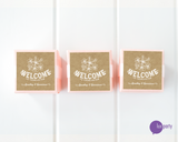 Three pink favor boxes with square brown kraft personalized welcome stickers affixed. Lux Party logo.